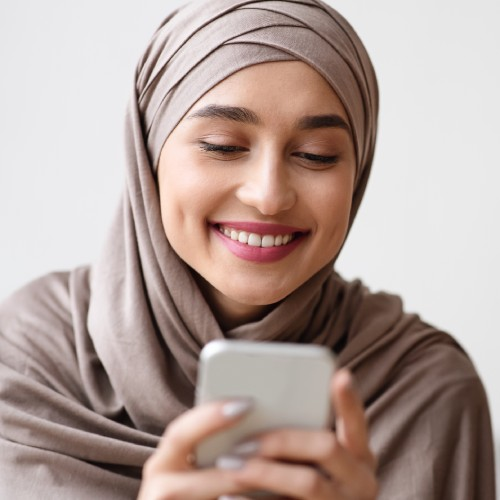 Happy muslim girl in hijab reading message on smartphone