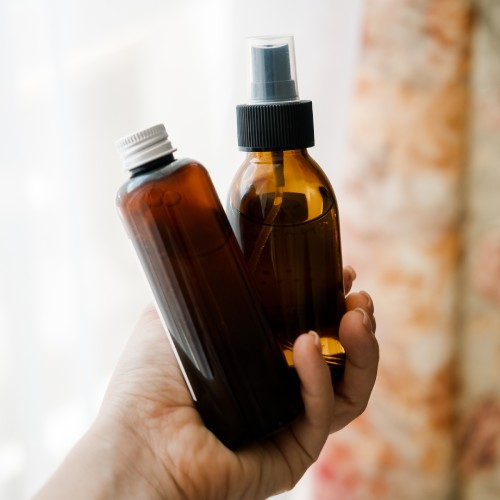 Two cosmetic bottles in womans hands